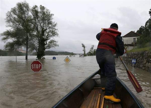 A member of the emergency services travels by boat along a flooded street in the Austrian village of Emmersdorf