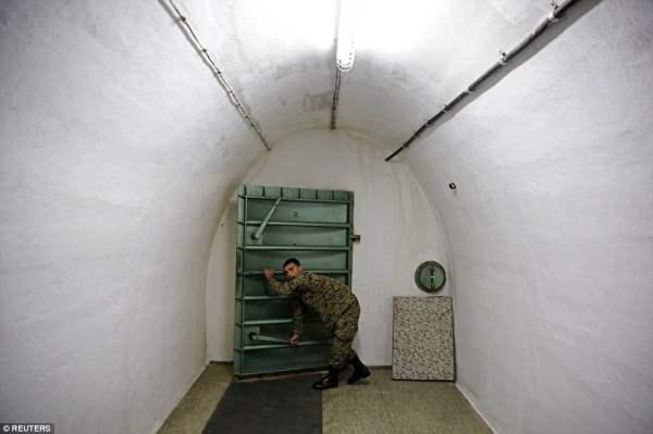 Солдат открывает металлическую дверь в бункере