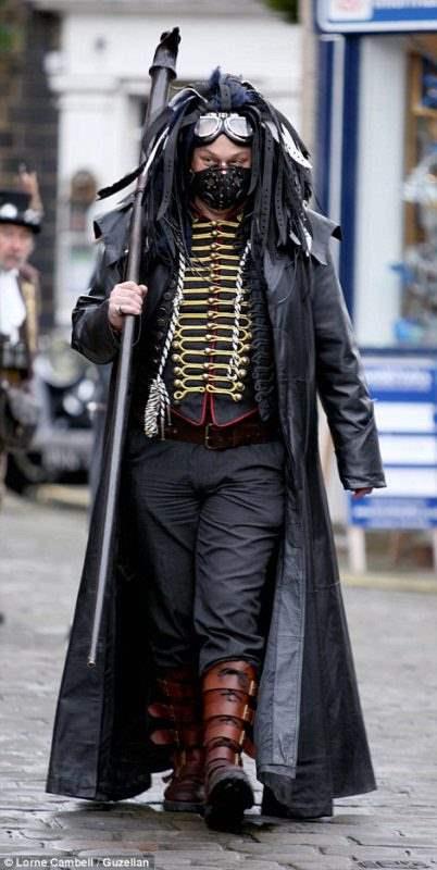 Мужчина в костюме стимпанк, с элементами кибер-готики ,в респираторе, длинном кожанном плаще, корсете и дредами из ремней.