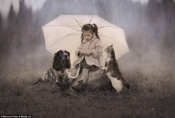 Девочка приютила двух животных под зонтиком в ненастную погоду