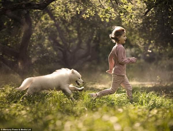 Девочка собакой играют в лесу