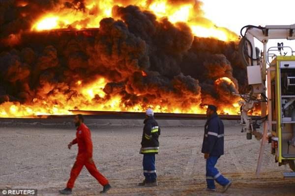 Пожарные стоят в стороне, когда пламя продолжает бушевать. Бак был поражен после атаки боевиков, которые  попыталась захватить порт