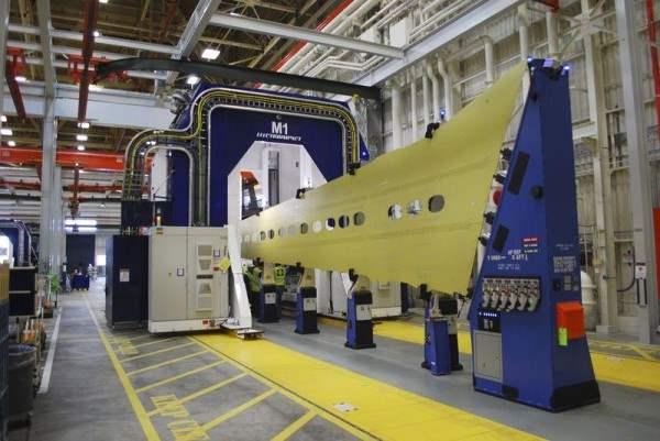Синяя, в форме подковы сборочная машина скользит по желтой панели крыла, которая станет частью 737 лайнера, на заводе Boeing в городе Рентон, штат Вашингтон. Снимок 12 марта 2015 года