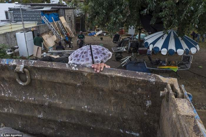 Фотограф из Торонто Аллен Агостино увлекся рассказами людей, живущими на пересечении восточного Бруклина и Квинса в Нью-Йорке. Район не подключен к системе канализации. Выше человек слазит с самосвала.