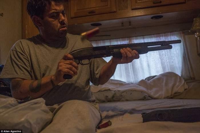 Житель района Нью-Йорка проверяет дробовик. Спать без оружия здесь нельзя.