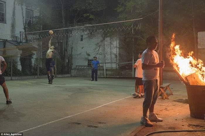 Один человек стоит у горящей бочки. в тот момент, как остальные играют в волейбол.