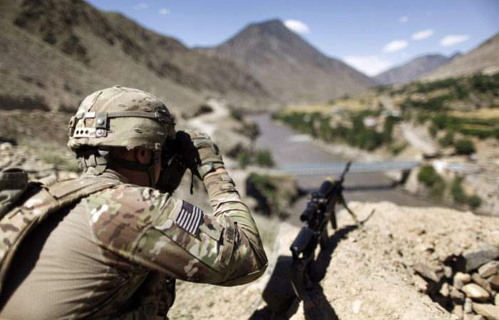 A soldier from the U.S. Army scans across the border at houses in Pakistan during a patrol near Dokalam village