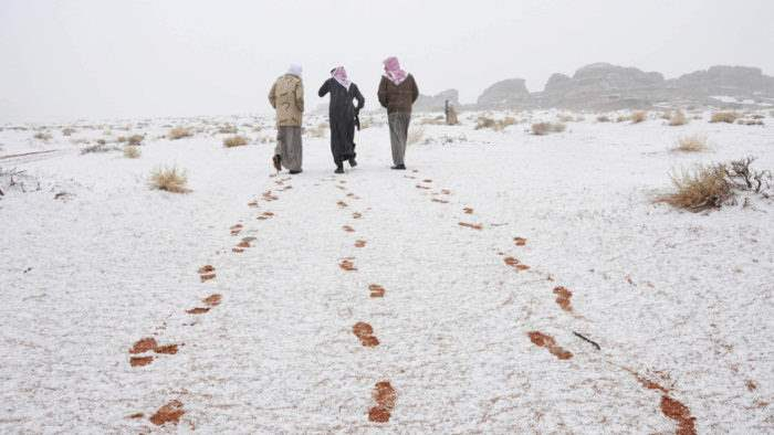 Saudi men walk as their footprints are seen after a snowstorm in Alkan village, west of Saudi Arabia December 13, 2013.  REUTERS/Mohamed Alhwaity (SAUDI ARABIA - Tags: ENVIRONMENT TPX IMAGES OF THE DAY)