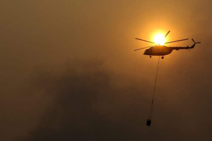 Вертолет помогает в тушении пожара в Индонезии.