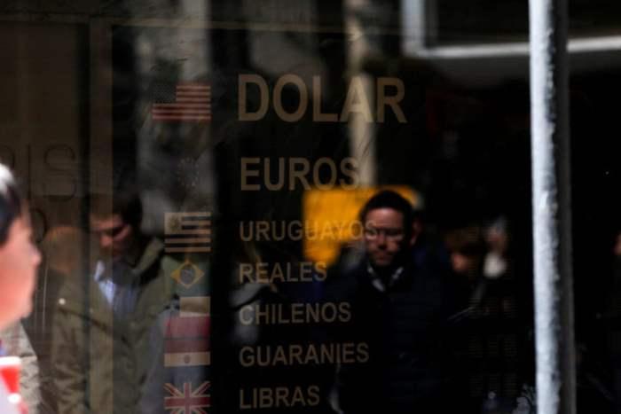 Люди проходят мимо пункта обмена валют