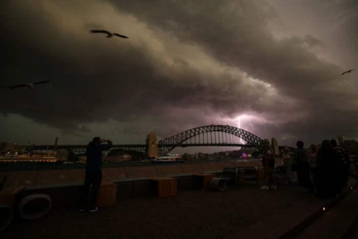 Молния в небе над мостом Харбор-Бридж в Сиднее, Австралия.