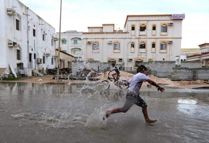 Дети из местного района играют в придорожной луже, накопленной от дождя, принесенного Циклоном Любань в Салале, Оман.