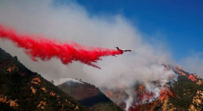 Самолет тушит пожар в Малибу, штат Калифорния.