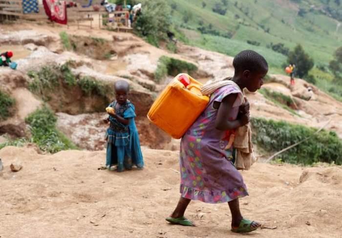 Девочка несет канистру с водой