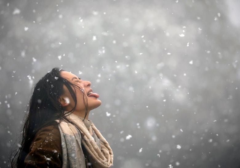 Женщина пытается поймать снежинки