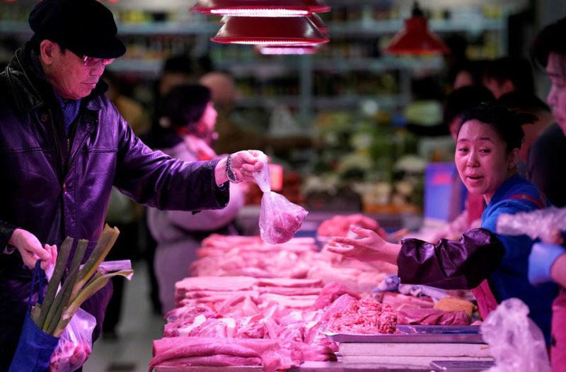 Клиент покупает свинину на рынке в Пекине, Китай.