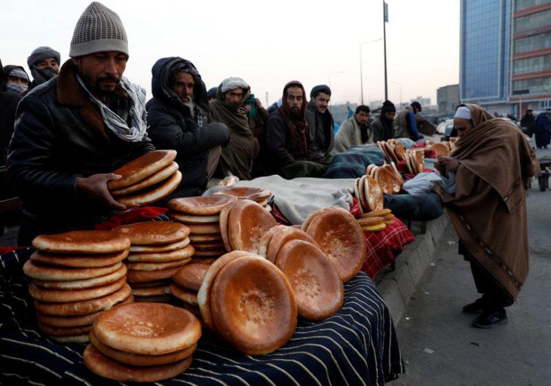 Мужчина покупает хлеб на рынке