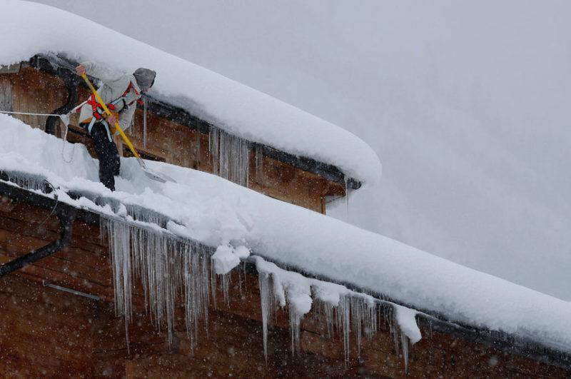 счищает снег с крыши