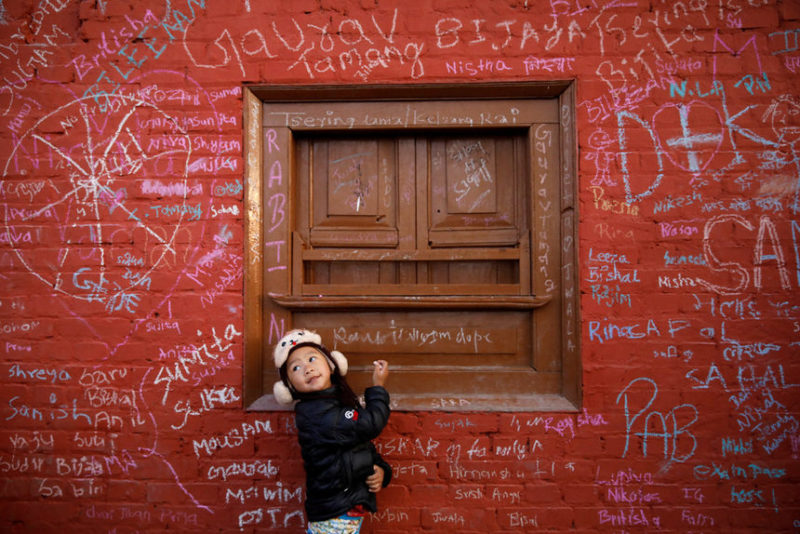 Девочка пишет на стене храма