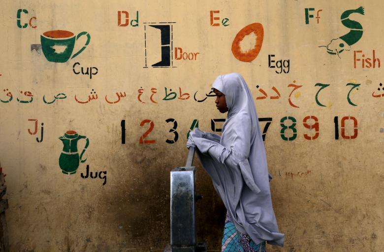 Девушка набирает воду из колонки