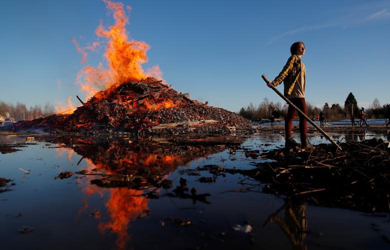 Девушка стоит перед горящей кучей