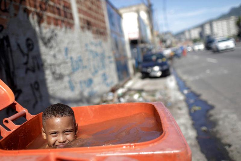Мальчик играет в мусорном баке