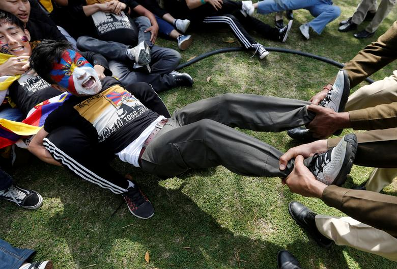 Полицейские задерживают тибетца