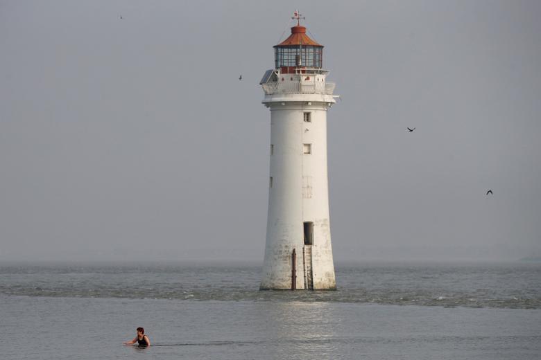 Женщина плавает в море перед маяком Perch Rock