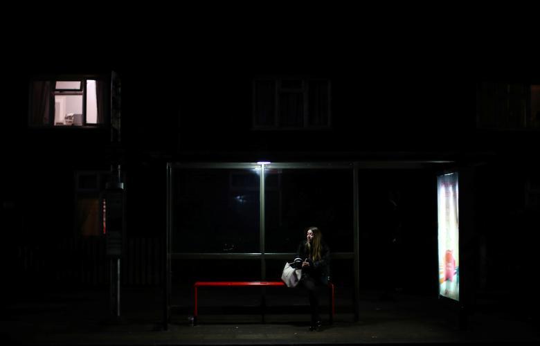 Женщина сидит на автобусной остановке
