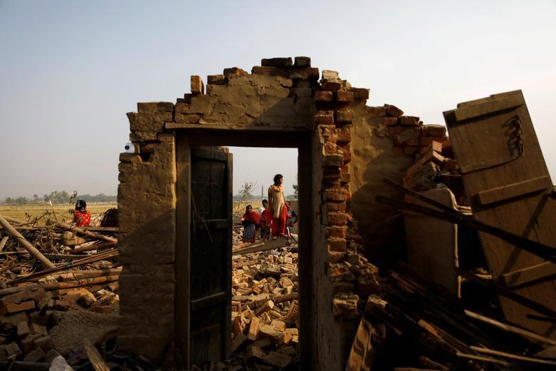 Жители деревни стоят на руинах