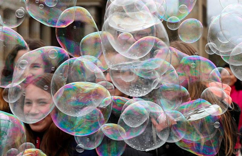 Люди весело проводят время с мыльными пузырями