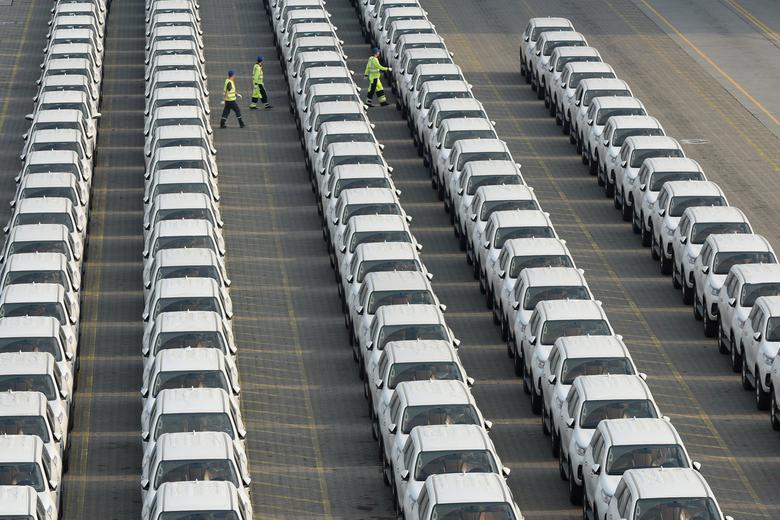Рабочие гуляют среди вновь прибывших импортных автомобилей