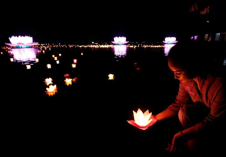 Буддистка выпускает свечу в озеро