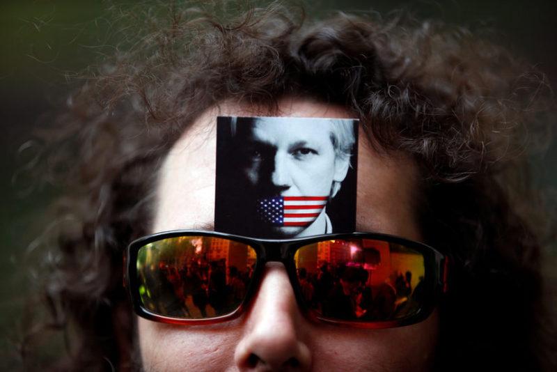 Демонстрант несет фотографию Джулиана Ассанжа