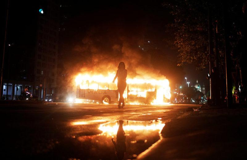 Женщина и горящий автобус в Бразилии.