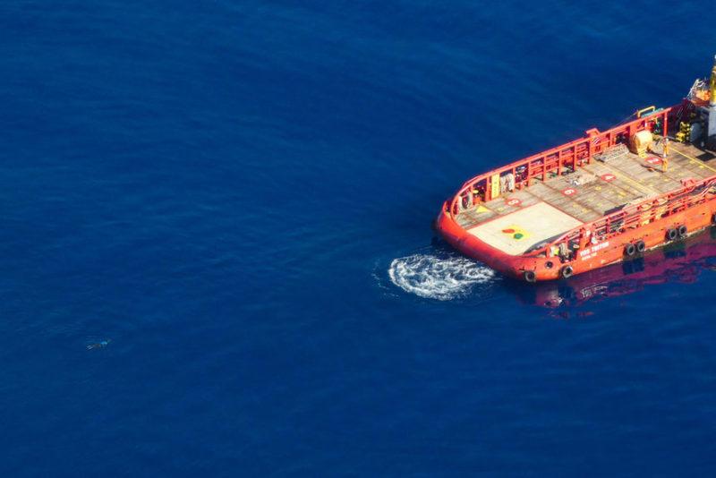 Мигрант плывет к торговому судну