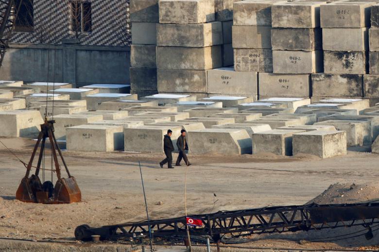 Мужчины проходят мимо бетонных опор
