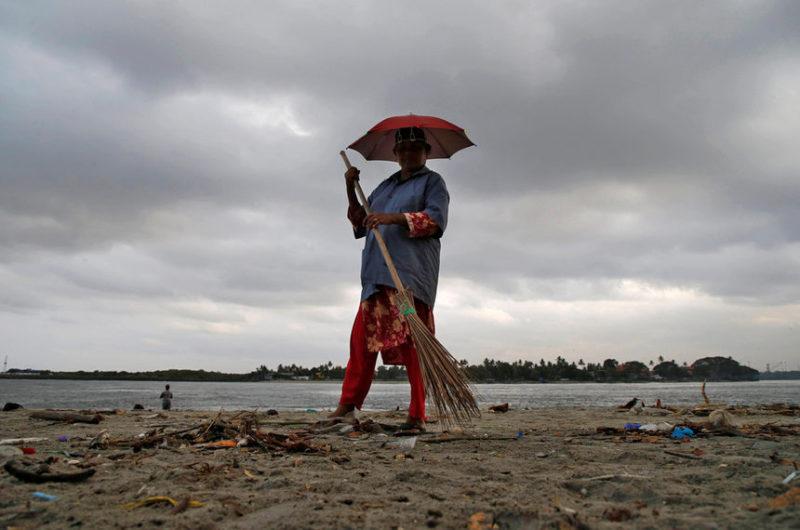 Рабочий очищает пляж в Кочи, Индия.
