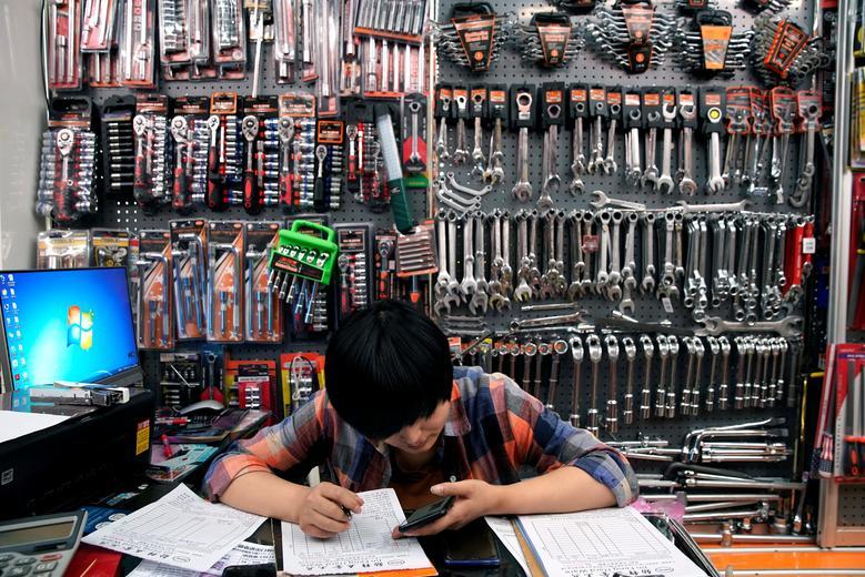 Сотрудник сидит в киоске, который продает инструменты.