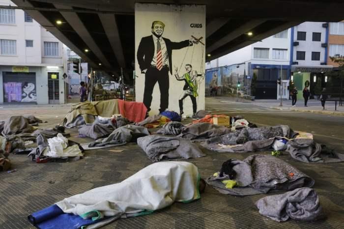 Бездомные люди спят под мостом