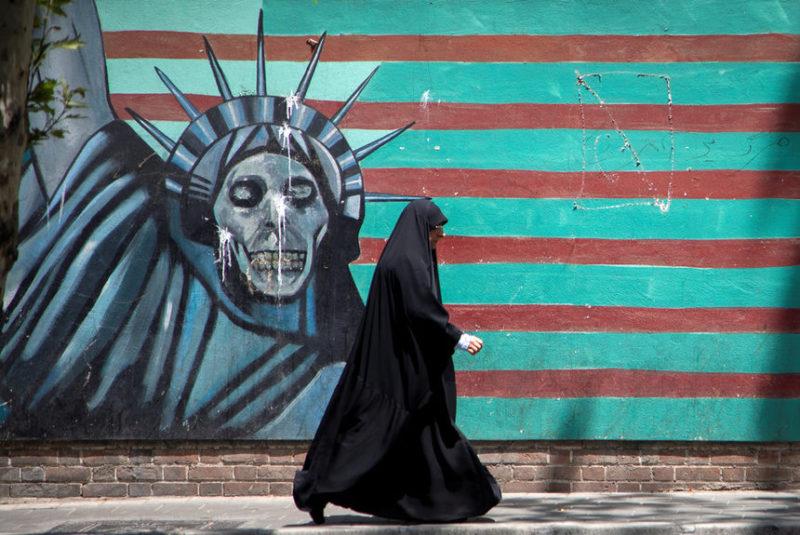 Женщина идет рядом с изображением Статуи Свободы