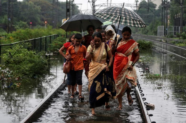 Пассажиры идут по заболоченным железнодорожным путям