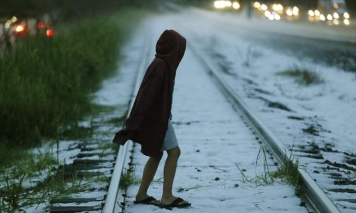 Мальчик пересекает железнодорожные пути после сильного града