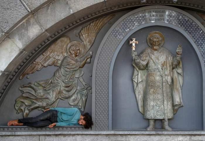 Мужчина отдыхает возле скульптуры Святого Владимира