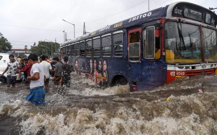 Общественный автобус пробивается сквозь паводковые воды