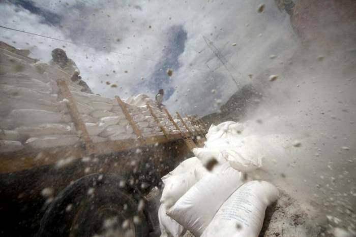 Рабочие утилизируют мешки с пшеничной мукой