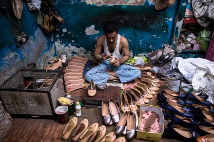 Сапожник наносит клей на обувь
