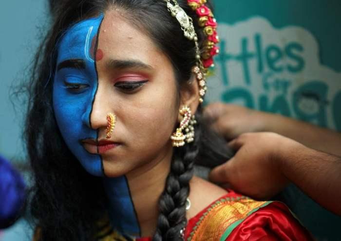 Студентка делает макияж перед тем, как принять участие в культурном мероприятии