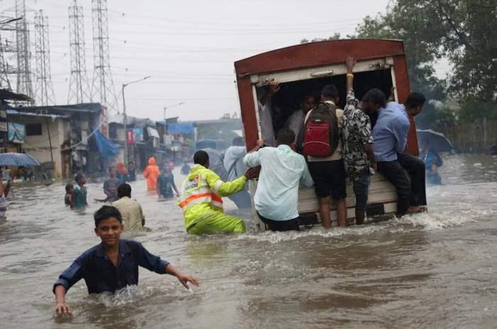 Люди едут на грузовике по затопленной дороге
