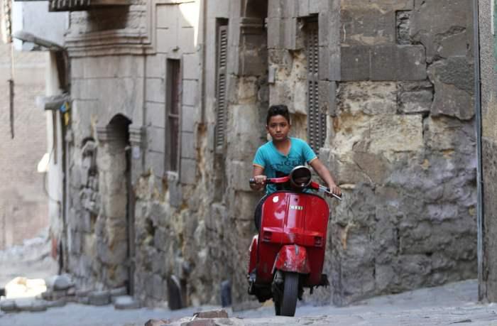Мальчик проезжает на мотоцикле